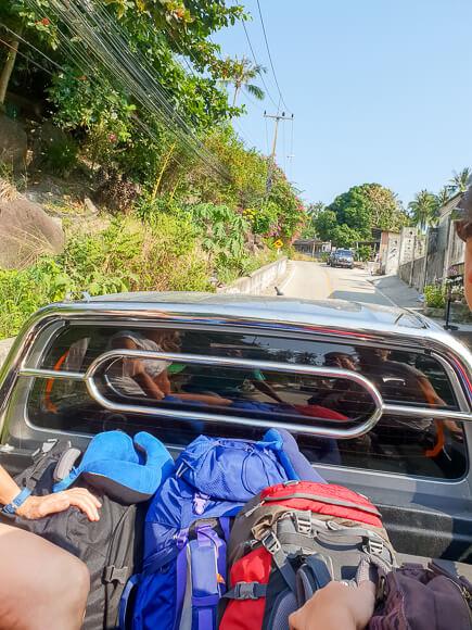 Rucksäcke auf Ladefläche von Pick-Up, der eine Straße hochfährt