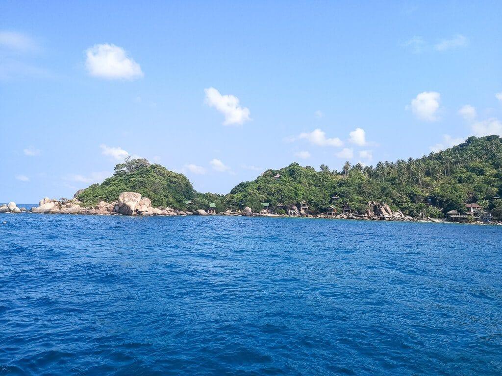 grüne Insel und Felsen im Meer