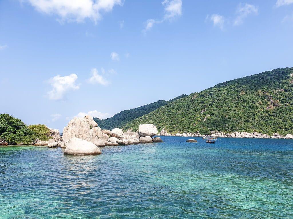 Felsen im Wasser vor einer grünen Insel