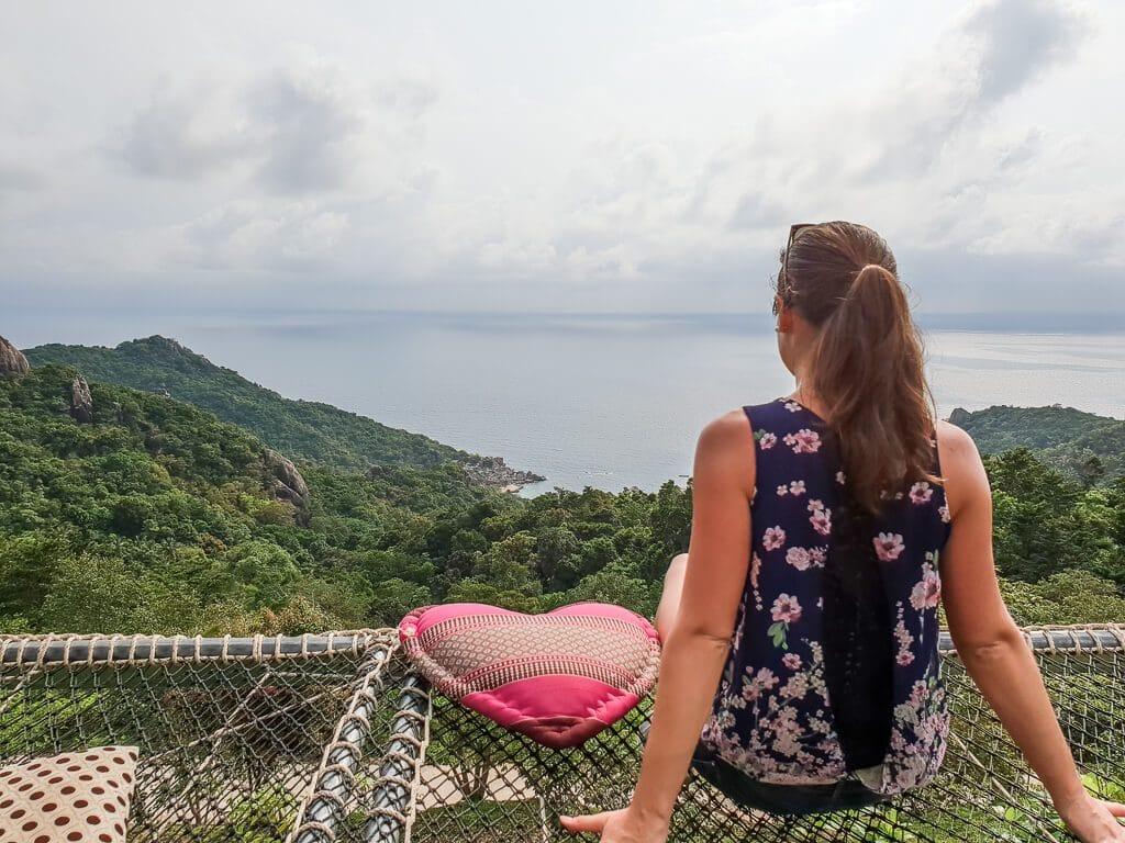 Frau sitzt auf Netz über den Bäumen mit Blick über eine grüne Insel und das Meer