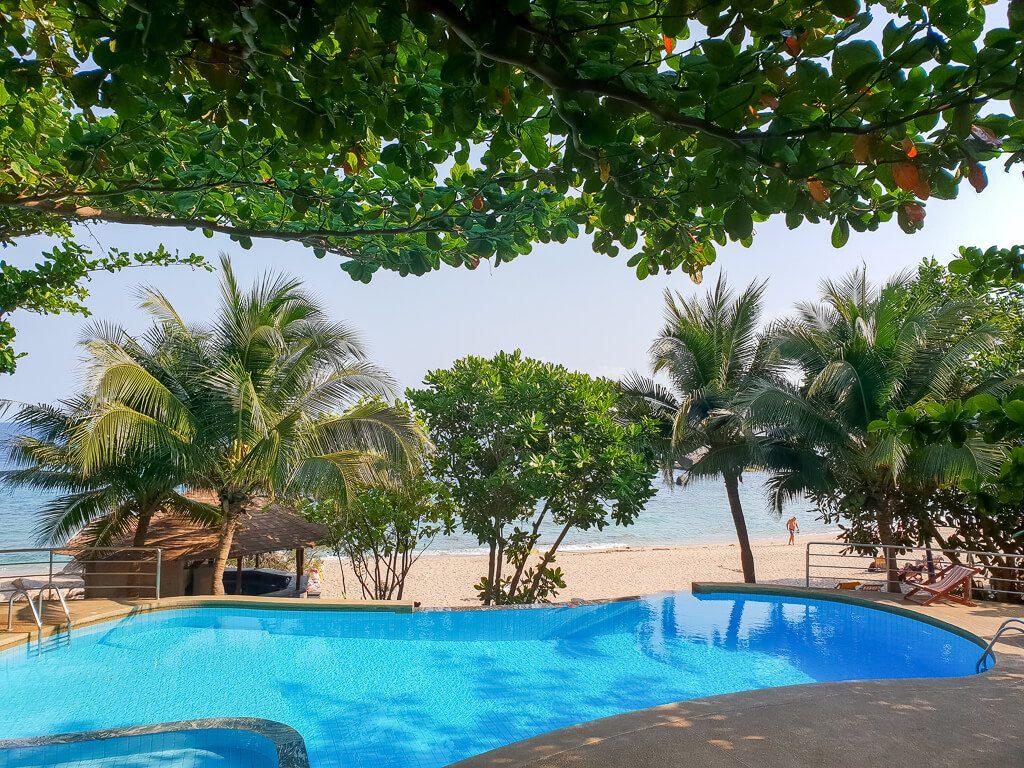 Pool umgeben von Bäumen und Palmen, dahinter schimmert das Meer und der Strand hindurch