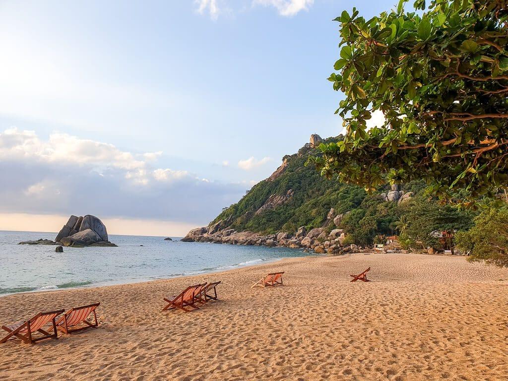 Liegestühle am Sandstrand, dahinter ein grüner Hügel und das Meer