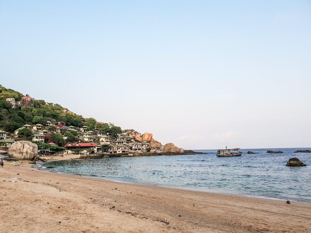 Strand in einer Bucht mit grünen Hügeln und Häusern am Hang