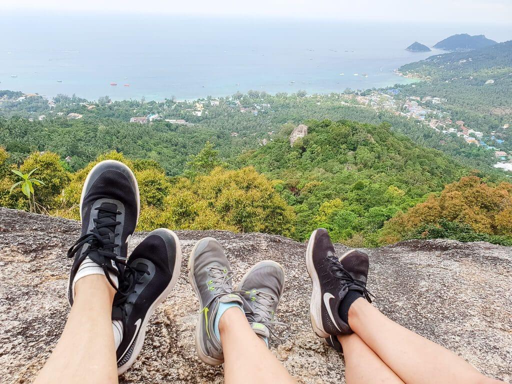 Frauen sitzen auf einem Felsen, sichtbar sind nur die Unterschenkel und Schuhe mit Blick auf den Wald und das Meer