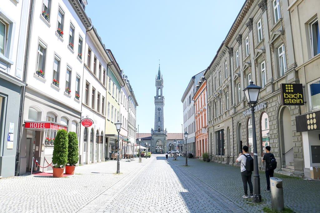 Innenstadt mit Häuserreihen auf beiden Seiten, in der Mitte im Hintergrund ein Kirchturm