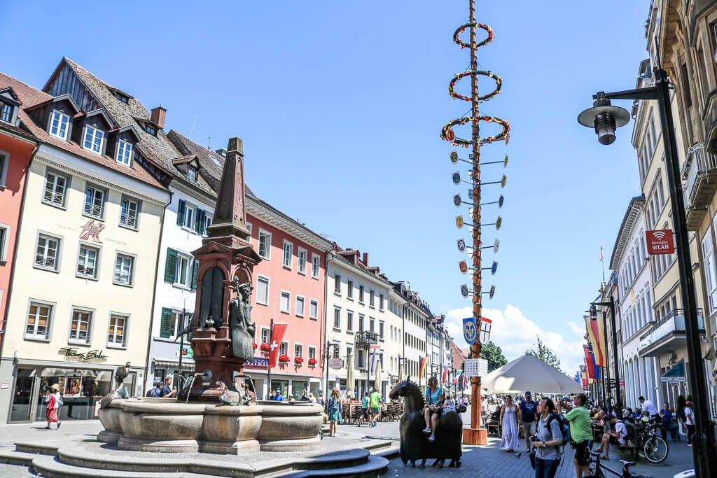 Marktplatz Konstanz mit einem Brunnen und bunten Häusern auf beiden Seiten, in der Mitte ein Maibaum