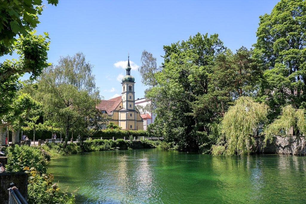 Ausläufer des Bodensee mit grünlichem Wasser umgeben von Bäumen, in der Mitte eine Kirche