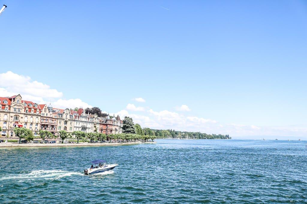 kleines Boot fährt auf dem Bodensee - am linken Ufer eine Häuserreihe