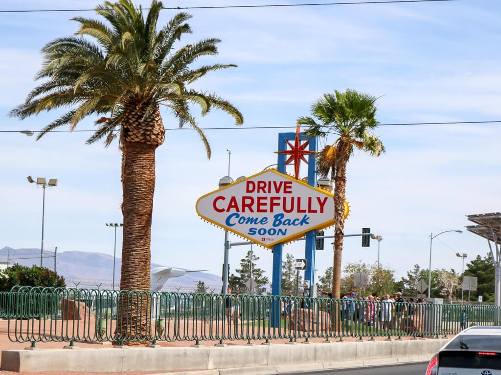 """Las Vegas Sign mit Aufschrift """"Drive Carefully - Come Back soon"""". Rund um das Schild verläuft eine Straße mit zwei hohen Palmen"""