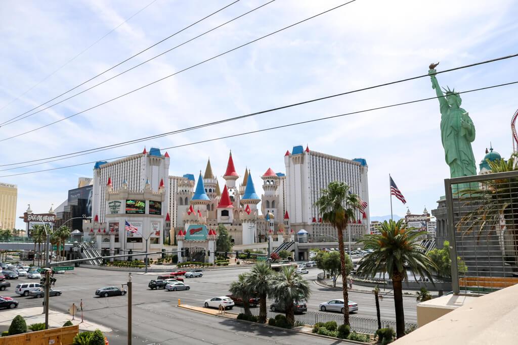 Blick über eine befahrene Straße auf ein Hotel, das aussieht wie ein Schloss mit Türmen in rot und blau; rechts daneben ist eine Freiheitsstatue zu erkennen