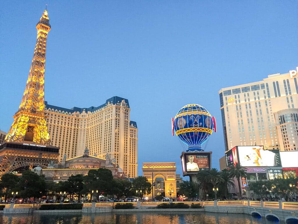 links ein Nachbau des Eiffelturm, daneben ein Gebäudekomplex, mit Triumphbogen und Heißluftballon-Nachbau. Es ist Dämmerung und die Gebäude sind beleuchtet