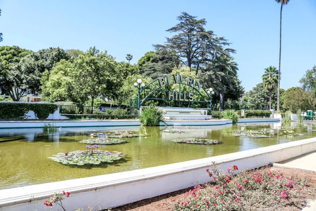 """kleiner, künstlicher Teich mit Seerosen und Einfassung aus hellem Stein - an der hinteren Seite ein grüner Bogen mit Schriftzug """"Beverly Hills"""""""