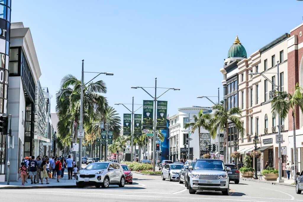 Rodeo Drive / Beverly Hills: vierspurige Straße mit Autos - zu beiden Seiten luxuriöse Geschäfte, Palmen und Menschen auf den Gehwegen.