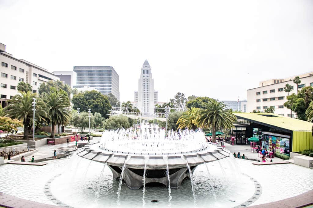 runder Springbrunnen im Vordergrund, dahinter ist die City Hall Los Angeles und einige Palmen zu sehen