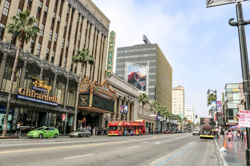 """Blick über eine breite Straße mit einem historischen Gebäude links mit der Aufschrift """"Ghirardelli"""", rechts ein Gehweg mit den Sternen des Walk of Fame"""