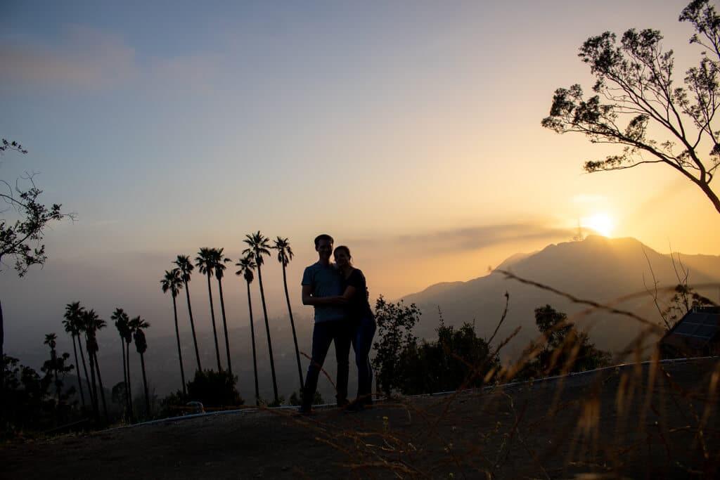 Sonnenuntergang gegenüber des Hollywood-Sign - Paar steht vor Palmen