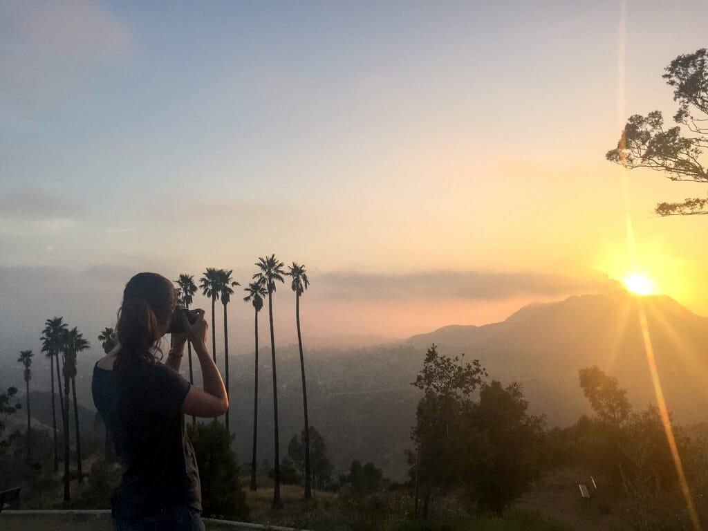 Frau fotografiert einen Sonnenuntergang hinter Palmen und einem Hügel