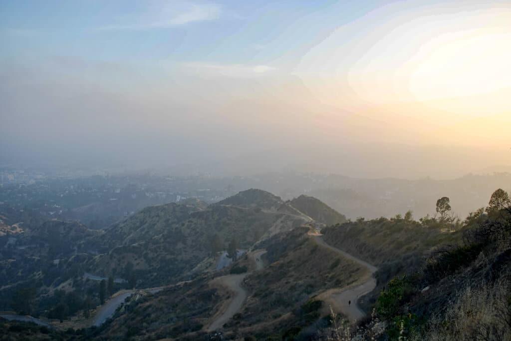 Wege führen einen Hügel hinauf - dahinter der Sonnenuntergang