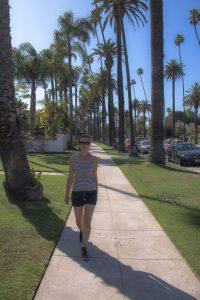 Beverly Hills - Frau läuft über Gehweg mit Palmen