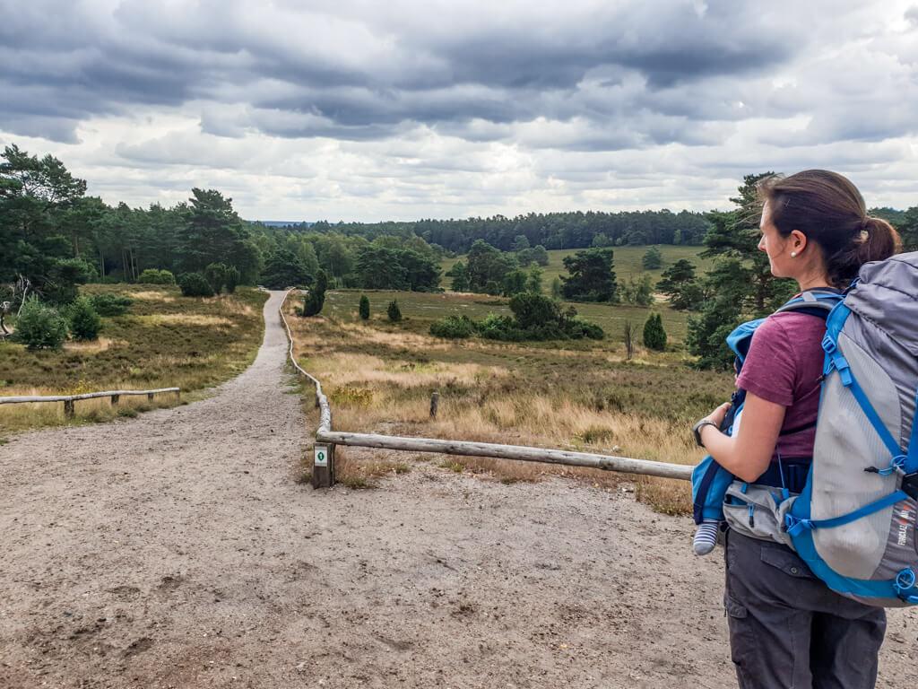 Frau mit Wanderrucksack steht auf einer Erhebung mit Blick in die Heidelandschaft