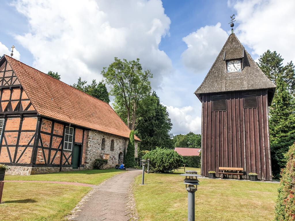 Blick über eine Wiese mit einem schmalen Weg zu einem hölzernen Glockenturm auf der rechten Seite und einem Fachwerkgebäude auf der linken Seite