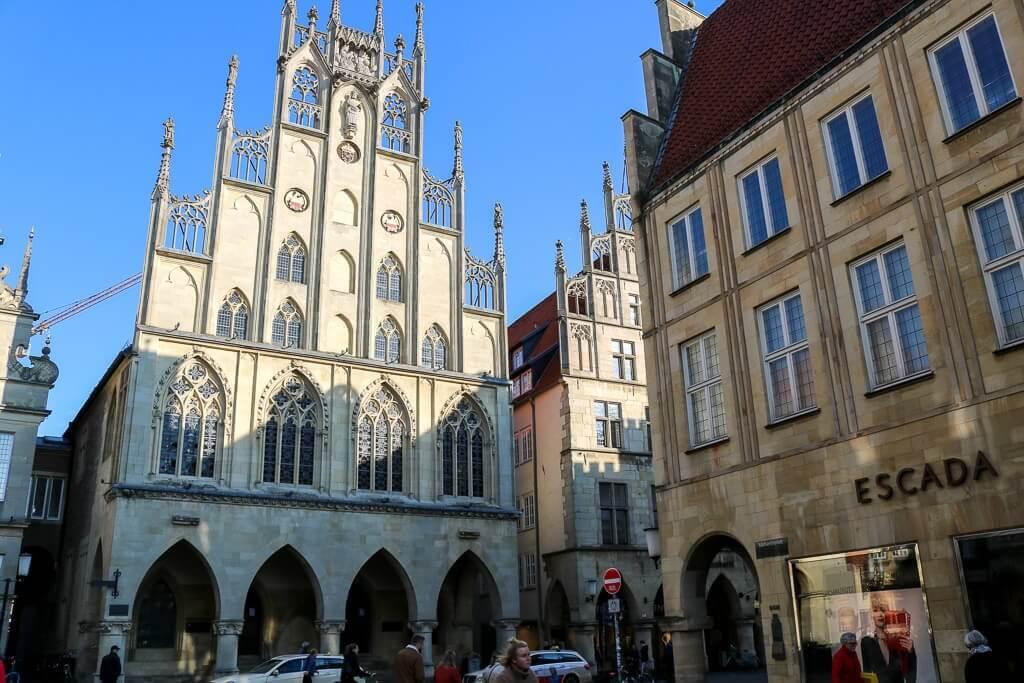 Blick auf das Rathaus von Münster: Innenstadtbereich mit Blick auf ein kunstvoll verziertes Giebelhaus mit Bogengängen und kunstvollen Glasfenstern.