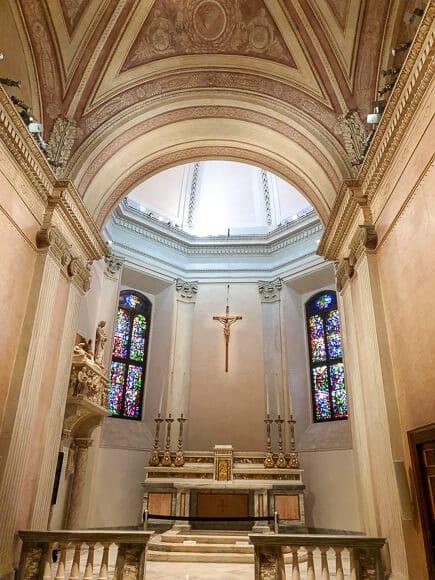 Altarraum in einer kleinen Kapelle mit Buntglasfenstern und Kreuz