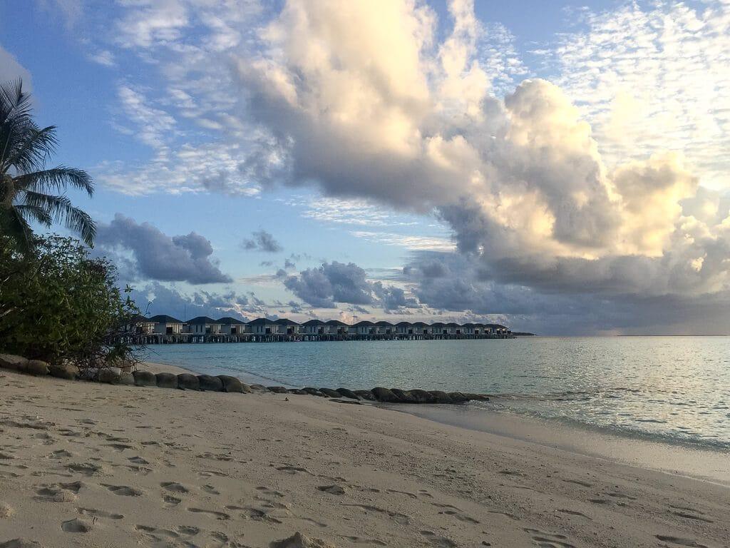 Malediven - Sandstrand mit Palmen, rechts davon das Meer, im Hintergrund Wasservillen