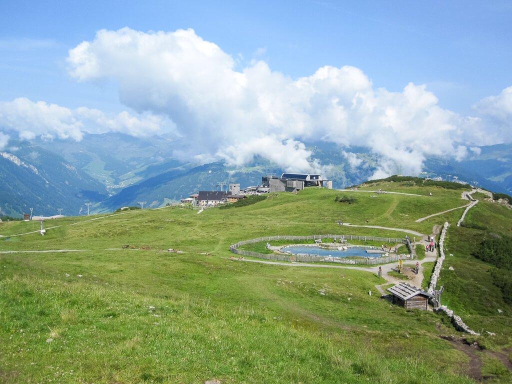 Kleiner Bergsee inmitten von grünen Wiesen - eine Gondelstation