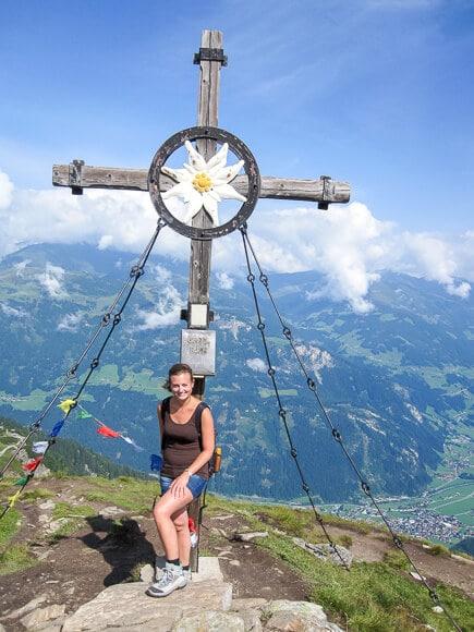 Frau steht an einem Gipfelkreuz mit Ausblick ins Tal - am Gipfelkreuz oben ein großes Edelweiß