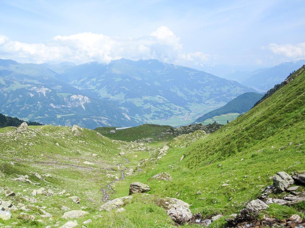 kleiner Bach in der Mitte umgeben von Wiese und Felsen - im Hintergrund sind grüne Berge zu sehen