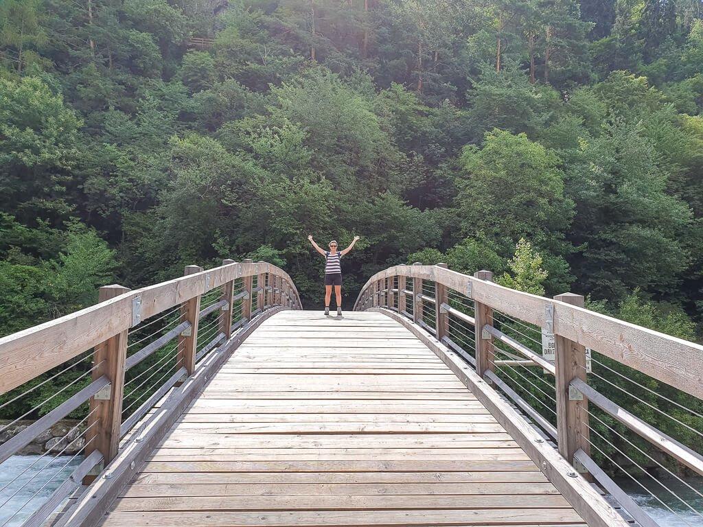 Frau steht mitten auf einer gebogenen Holzbrücke über einen Fluss