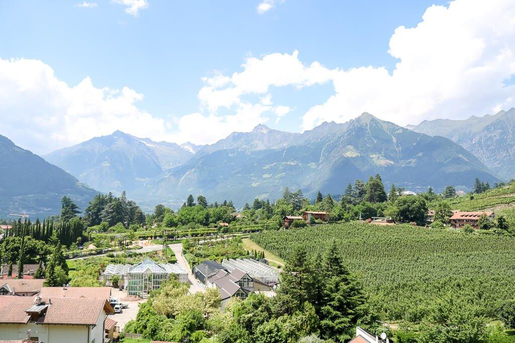 Gärten und Weinberge vor massiven Bergen