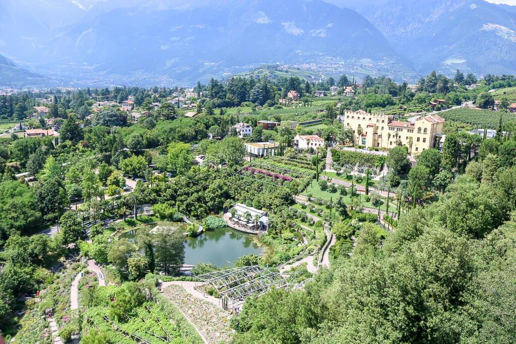 Schloss auf einem Hügel mit Treppenförmigen Terrassen bis hin zu einem See - alles umgeben von grünen Bäumen und Bergen