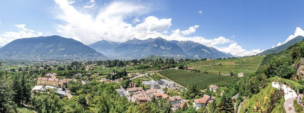 Panoramablick über Meran mit Wiesen und Bergen im Hintergrund
