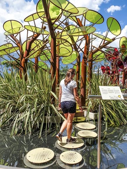 Frau überquert Steine in einem See hin zu einer kleinen Insel mit Kunstwerken aus Glas