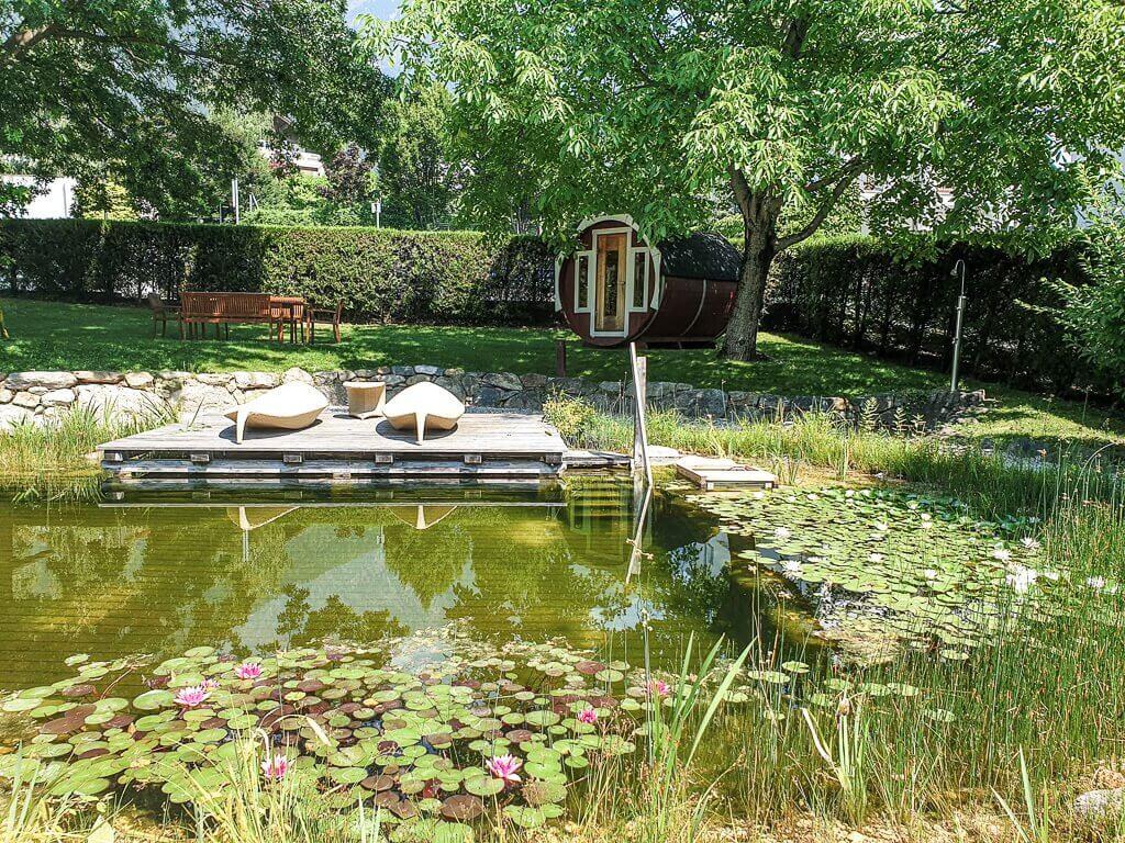 Schwimmteich mit Seerosen und einem kleinen Steg, dahinter eine Wiese mit Fass-Sauna