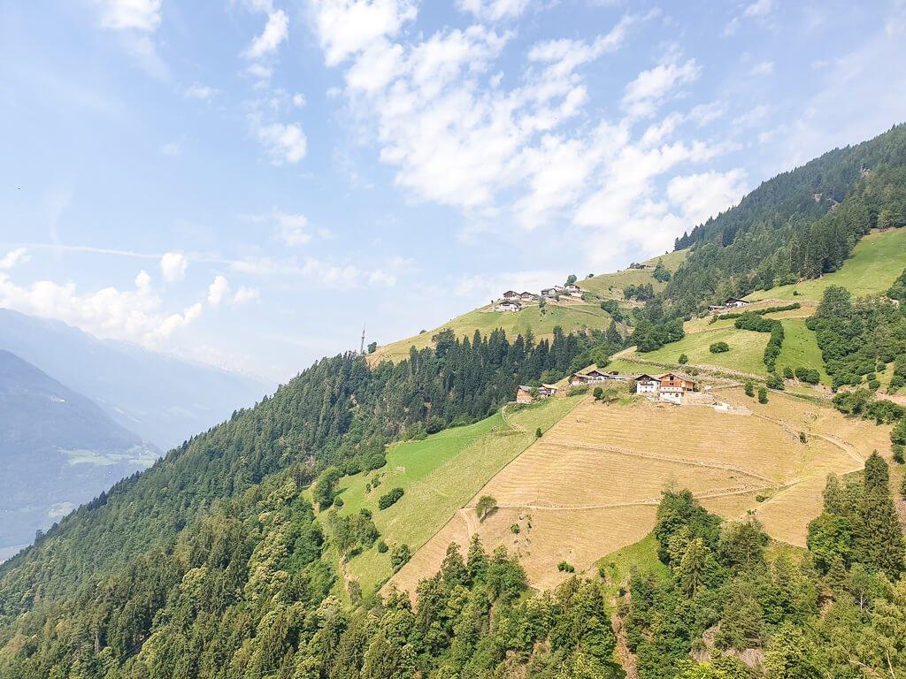 Blick auf einen Berg mit Feldern und der Bergstation einer Gondel