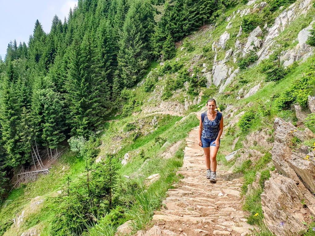 Frau steht auf einem schmalen Bergweg, im Hintergrund Wald, links ein abfallender Hang mit Wiese