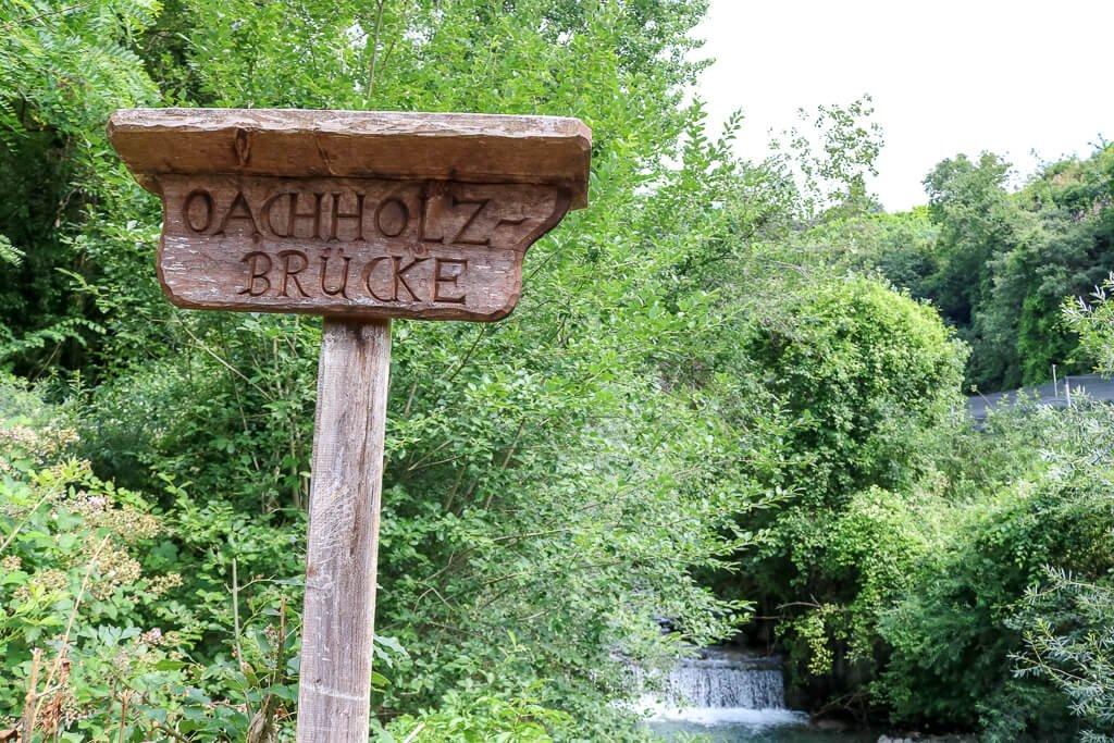 Holzschild auf einer Brücke mit Blick auf einen kleinen Wasserfall
