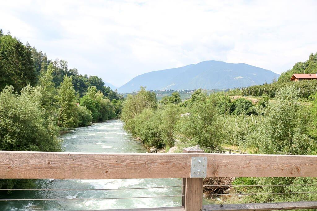 Holzbrücke über einem Fluss, rechts und links Wald