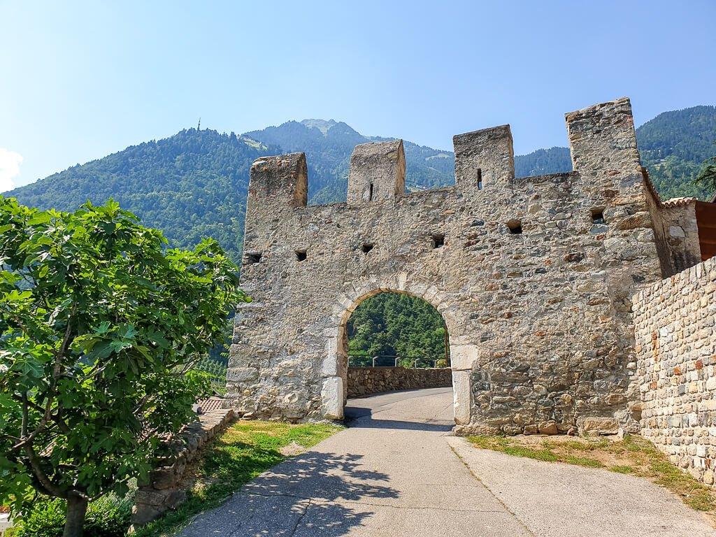alter Torbogen mit Zinnen einer Burg - Berge im Hintergrund