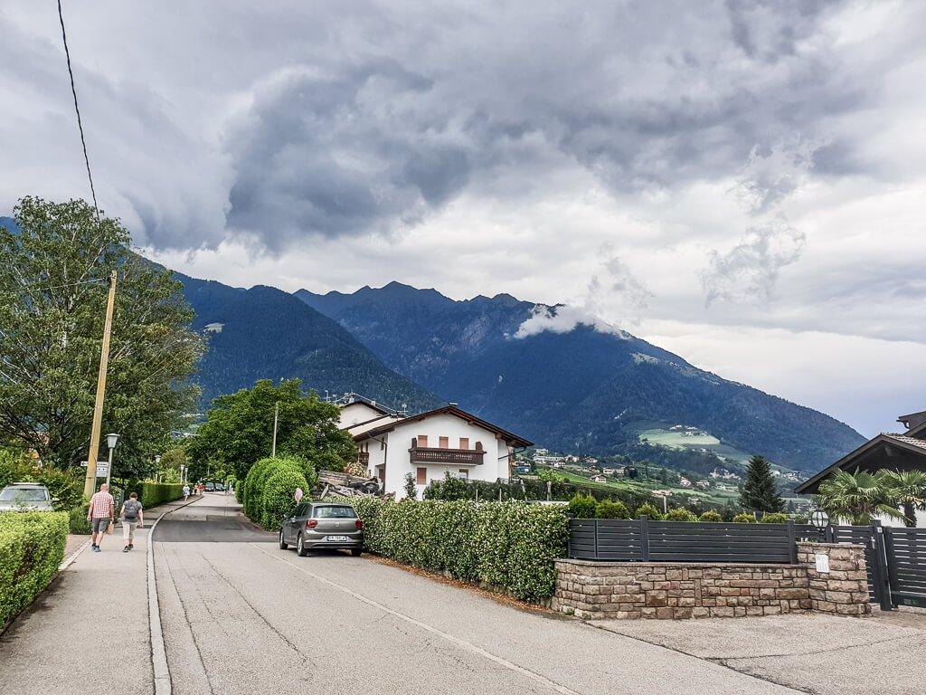Straße mit Häusern am Rand - im Hintergrund begrünte 'Berge