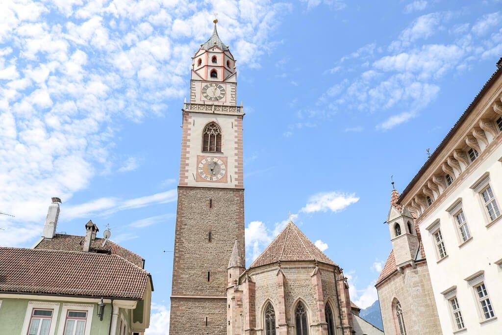 Kirchturm umgeben von blauem Himmel und kleineren Häusern