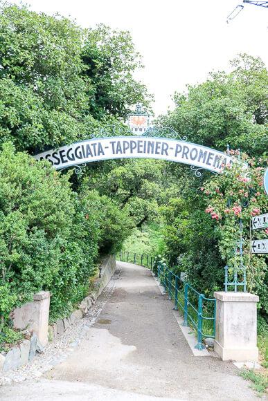 """Weg umgeben von Bäumen mit Torbogen """"Tappeiner-Promenade"""""""