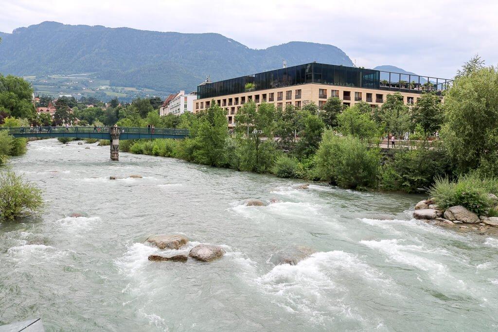 Fluss mit Steinen in der Mitte, am Rande die Therme Meran