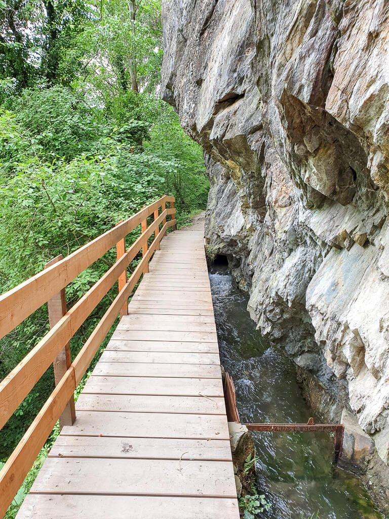 Links ein Felsen, daneben ein kleiner Fluss mit einer Holzbrücke