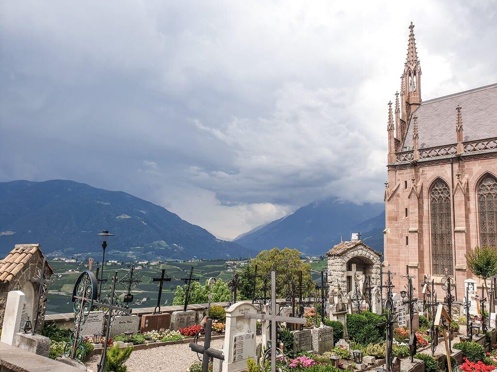 Friedhof mit Kirche und Grabsteinen, im Hintergrund Berge und dunkle Wolken