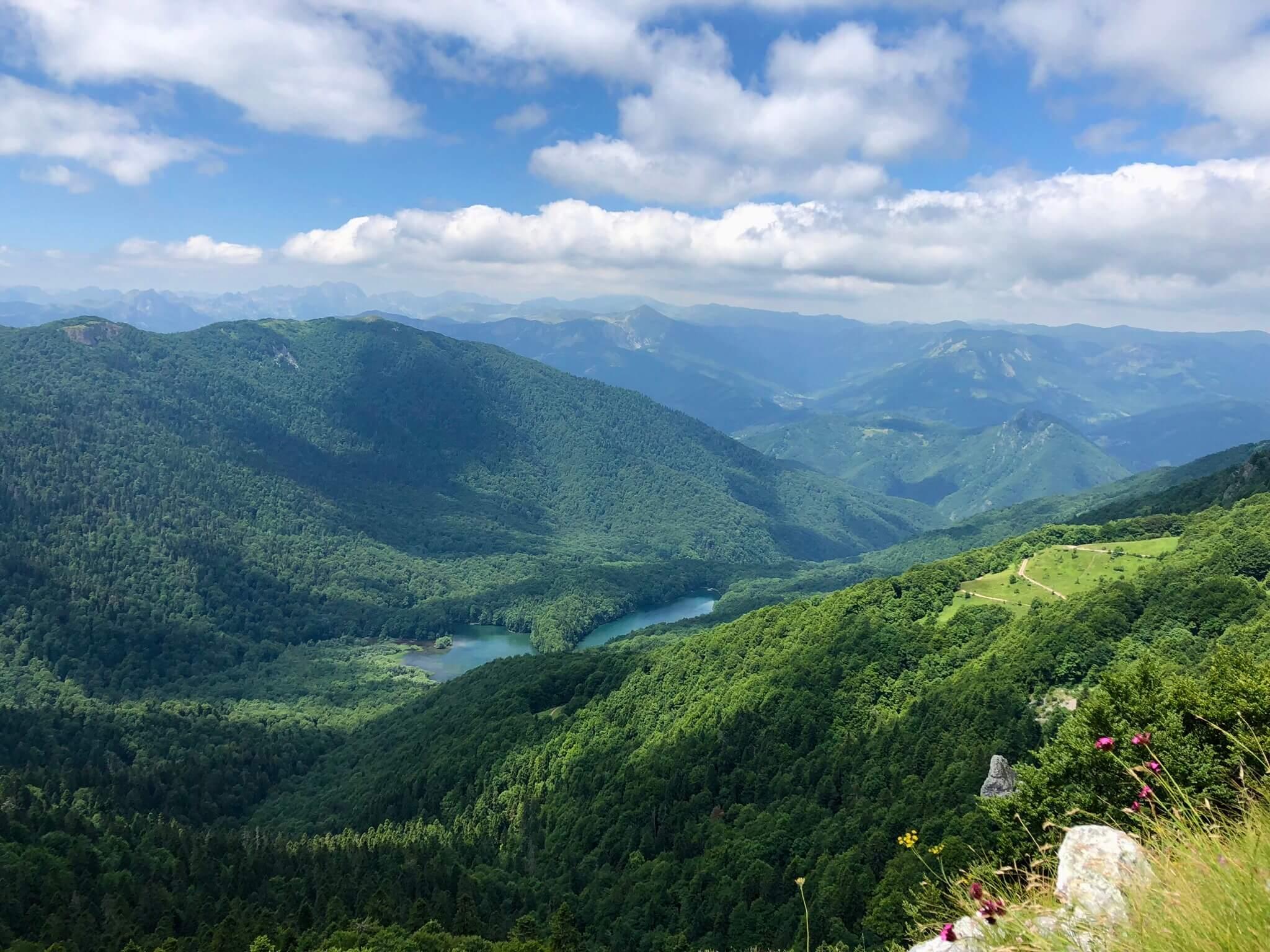 Ausblick über grüne Berge und Seen bei leicht bewölktem Himmel