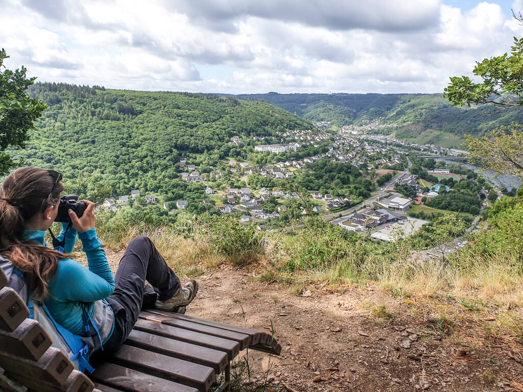 Frau sitzt auf einer Bank und fotografiert das Moseltal
